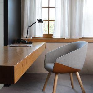 Podwieszane biurko o dużej powierzchni blatu, zestawione z prostym, tapicerowanym fotelem o kubełkowym siedzisku. Fot. Bejot
