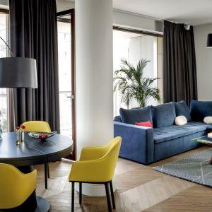 Żółte krzesła i błękitna sofa pomogły stworzyć przytulne wnętrze. Autorzy koncepcji Anna Koszela, Maria Widelak. Fot. Rafał Lipski
