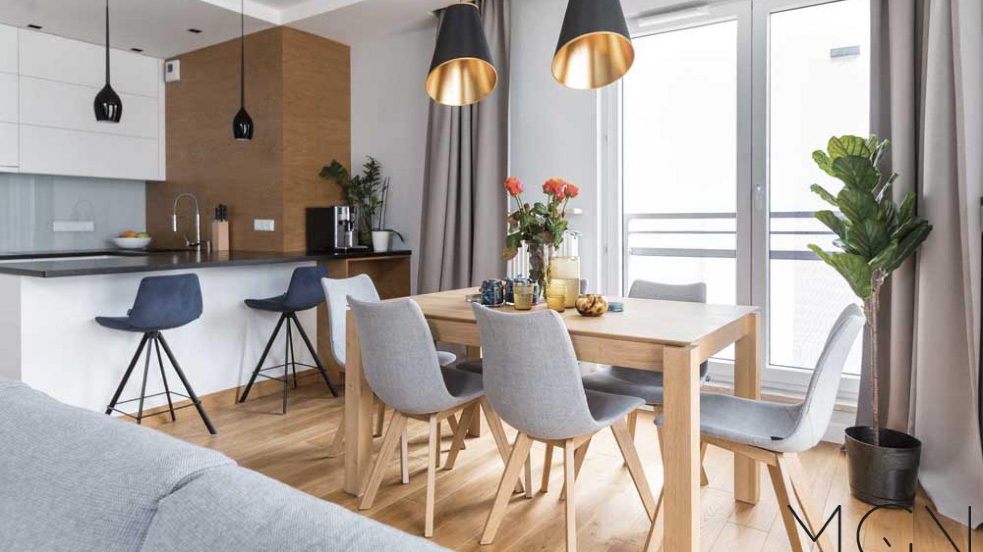 Praktycznym rozwiązaniem jst ustawiene na granicy kuchni i salonu stołu jadalnianego. Fot. Pracownia Architektoniczna MGN