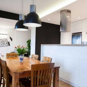 Drewniany stół i krzesła stanowią ciekawy kontrast dla białej zabudowy. Projekt Pracownia Architektoniczna MGN