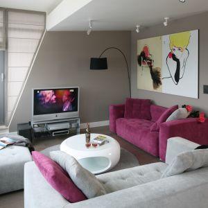 Czasem wystarczy sofa w żywym kolorze i ciekawe grafiki na ścianach, by nadać wnętrzu artystyczny klimat. Projekt Małgorzata Borzyszkowska. Fot. Bartosz Jarosz