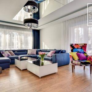 Duża, niebieska sofa dobrze prezentuje się w obszernym salonie. Realizacja Kwadrat Design Studio