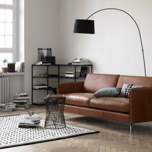Wygodna kanapa, duża lampa i etażerka z książkami. Fot. BoConcept