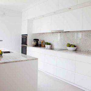 To granit, z którego są blaty i okładzina ściany, nadaje tej neutralnej kuchni z białą zabudową wyrazisty charakter. I zawsze wygląda nieskazitelnie! Fot. Pracownia Projektowa MGN