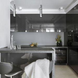 Tafla zmatowionego szkła na ścianie w ciągu roboczym jest niemal niewidoczna, dzięki czemu otwarta na część wypoczynkową kuchnia zyskuje salonowy charakter. Fot. Pracownia Projektowa MGN
