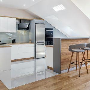 Blat i kuchenny bar w kolorach drewna pięknie kontrastują z bielą frontów. Fot. Studio Prestige/Max Kuchnie