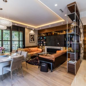 Salon od hallu oddziela regał zrobiony według projektu Viva Design, z chromowanym stelażem i półkami obitymi skórą. Fot. Viva Design