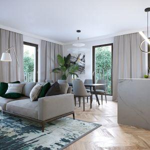 Kuchenna wyspa i sofa ustawiona tyłem do jadalni pozwalają podzielić wnętrze na strefy. Realizacja JMW Architekci