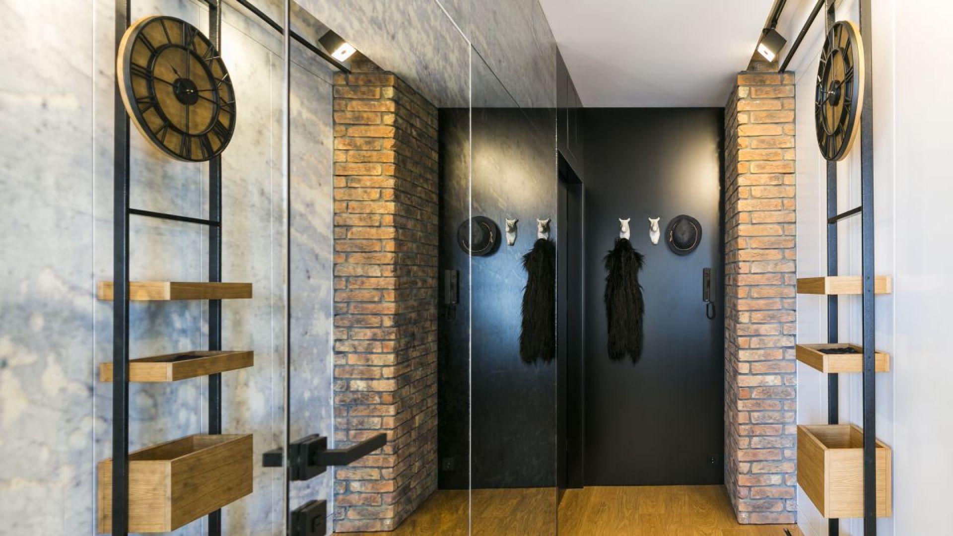 Zaraz po przekroczeniu progu mieszkania widać ręcznie wykonany, przesuwny regał ze stali i dębiny, zamocowany na metalowych szynach, na którym zawisł charakterystyczny dla stylu steampunkowego zegar. Projekt: 3DProjekt architektura.