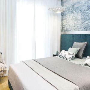 W sypialni, w której dominują biel i butelkowa zieleń, postawiono na welurową tkaninę o zdecydowanym, głębokim kolorze. Tapicerowane łóżko zwieńczono wezgłowiem ujętym w ramę z patynowanej blachy. Projekt: 3DProjekt architektura.