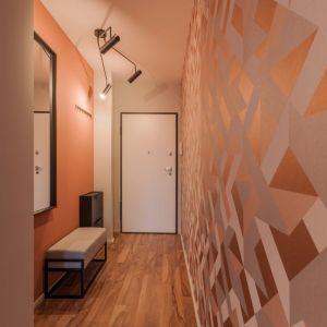 W przedpokoju, podobnie jak w salonie, jedną ze ścian zdobi motyw tapety, a przeciwną pomalowano w koralowym odcieniu. Projekt: pracownia Kodo. Fot. Pracownia Kodo