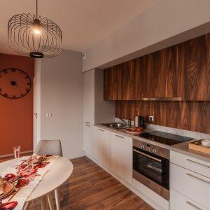 Drewniane fronty z wyraźnie zarysowanym usłojeniem sprawdzą się w kuchni. Realizacja - Pracownia KODO