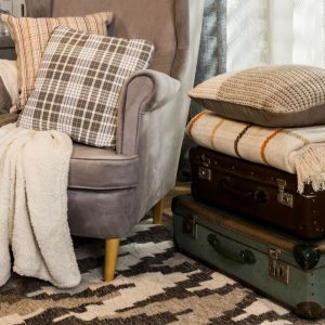 Miękkie dywany, pledy i koce to obowiązkowy element aranżacji w stylu cosagach. Fot. Agata