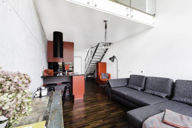 Industrialny apartament na warszawskim Mokotowie to propozycja dla miłośników loftowych wnętrz. Chłód betonu koresponduje z designerskim oświetleniem i wyposażeniem w kolorze nasyconej czerwieni.