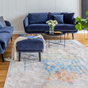 Niebieskie sofy pięknie komponują się z dywanem o rozbielonych kolorach. Realizacja Decoroom