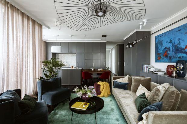 Dużą, oliwkową sofę zestawiono tu ze szmaragdowym dywanem i zgrabnymi fotelikami w morskim kolorze. Pięknie kontrastują z nimi karminowe krzesła. Autorką projektu tego wnętrza jest architektka Katarzyna Arsenowicz.