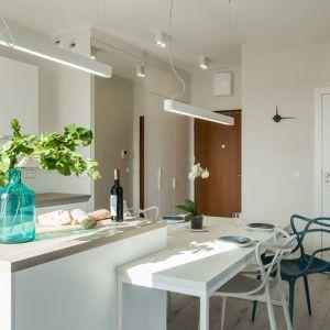 Wnętrze ocieplają naturalne akcenty – drewniane podłogi, blaty, drzwi, zieleń roślin i bogato rozmieszczone punktowe oświetlenie. Projekt: Kodo. Fot. Kodo