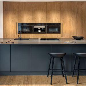 Wysokie szafy pokryte zostały fornirem dębowym, co nadało kuchni salonowego charakteru. Fot. Zajc