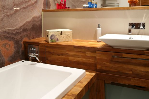 Dużą łazienkę, kolorystycznie ocieplają drewniane elementy wyposażenia. Wytrzymałe na działanie wilgoci drewno teakowe czyni wnętrze bardziej przytulnym.
