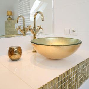 Pomiędzy oszczędnym minimalizmem a barokowym przepychem panuje idealna równowaga: złota mozaika zdobi jedynie rant blatu, a jego biała, ceramiczna powierzchnia eksponuje urodę szklanych mis umywalkowych. Fot. Bartosz Jarosz