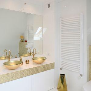 Klarowny charakter przestrzeni łazienki to efekt funkcjonalnego rozmieszczenia wyposażenia oraz ograniczenia palety barw do bieli i złota. Fot. Bartosz Jarosz