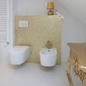 Białe sanitariaty umieszczone zostały na tle wykończonej mozaiką ściany. Idealnie dopasowany stylem i kolorem przycisk uruchamia spłuczkę podtynkową firmy Geberit. Fot. Bartosz Jarosz
