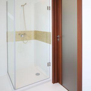 Narożna kabina prysznicowa została zamontowana na płaskim brodziku marki Koło, pas złotej mozaiki zdobi strefę prysznica. Fot. Bartosz Jarosz