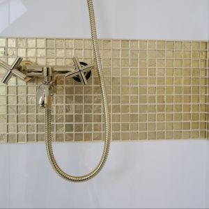 Cały zestaw armatury  został dopasowany do stylu oraz kolorystyki łazienki: bogate wykończenie w kolorze złotym równoważy prosta forma. Fot. Bartosz Jarosz