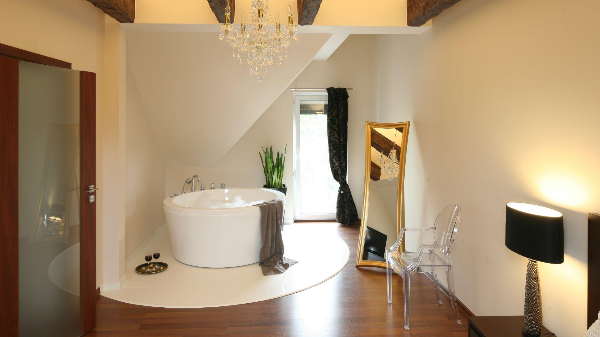 Strefa kąpielowa została częściowo przeniesiona do sypialni. Umieszczona w rogu wanna prezentuje się efektownie, a pozostałe elementy wystroju – lustro w złotej ramie, kryształowy żyrandol – tworzą klimat wytwornego salonu kąpielowego. Fot. Bartosz Jarosz