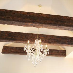 Typowe dla stylu rustykalnego – drewniane belki sufitowe w połączeniu z żyrandolem w  stylu glamour podkreślają pałacowy styl sypialni. Fot. Bartosz Jarosz