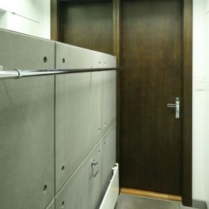 Do łazienki dla gości prowadzą drewniane drzwi w kontrastującym, ciemnym kolorze. Fot. Bartosz Jarosz