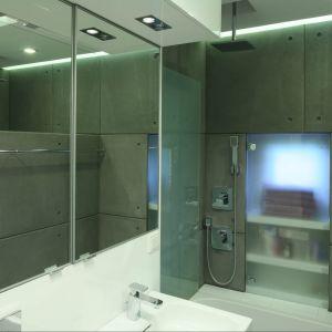 Przestrzeń łazienki dla gości optycznie powiększają duże lustra zamontowane w strefie umywalki.  Fot. Bartosz Jarosz