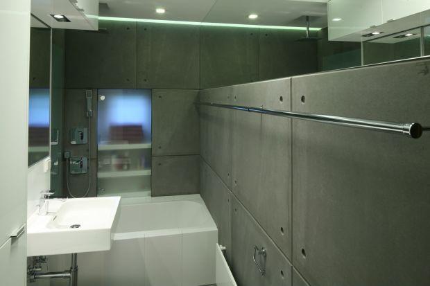 W aranżacji tej małej łazienki dla rodziny główną rolę odgrywa beton. Surowa, minimalistyczna stylistyka zapewnia perfekcyjny porządek i funkcjonalizm.