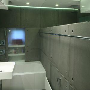Szare, betonowe płyty oraz elementy ze stali nierdzewnej czynią aranżację łazienki dla rodziny bardzo klimatyczną. Fot. Bartosz Jarosz