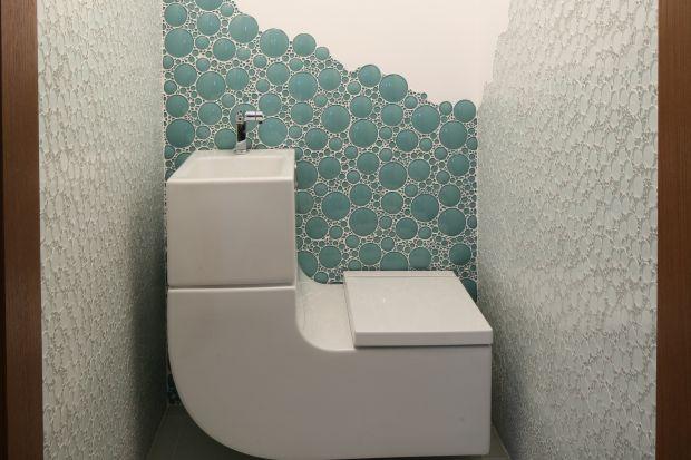 Patrząc na fotografie, w pierwszej chwili trudno się zorientować, że to podwójna łazienka gościnna. Na ścianach i podłodze w obu pomieszczeniach jest szkło w postaci mozaiki.