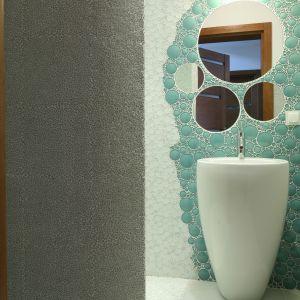 Ściany łazienki z prysznicem są wykończone mozaiką ze szkła: łamaną oraz okrągłą. Lustra zamówiono u szklarza. Fot. Bartosz Jarosz