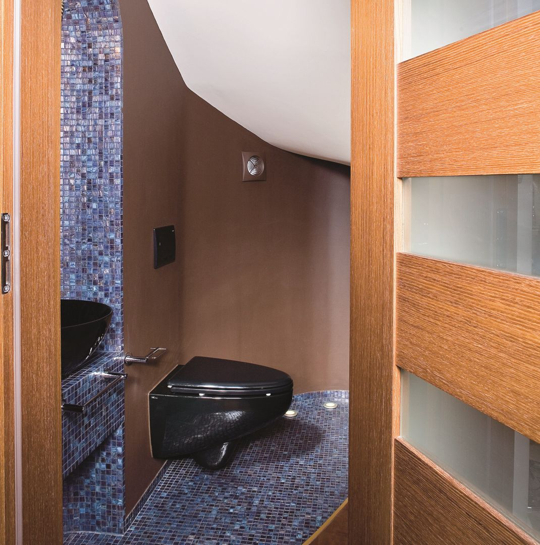 Gościnne WC pod schodami - aby można było wygodnie stanąć przy umywalce, wykonano małe przebicie ściany do sąsiedniego pomieszczenia. Proj. Joanna Liss. Fot. Bartosz Jarosz