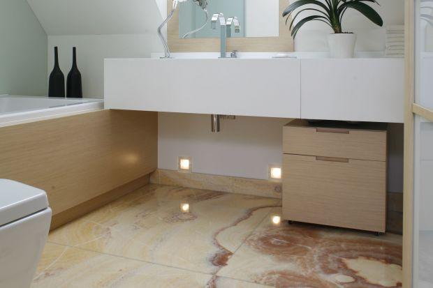 Biel i kamienna podłoga w jasnym wybarwieniuczynią tę łazienkę bardzo lekką. Taka aranżacja wnętrza dodaje energii rano, natomiast wieczorem – koi i uspokaja.
