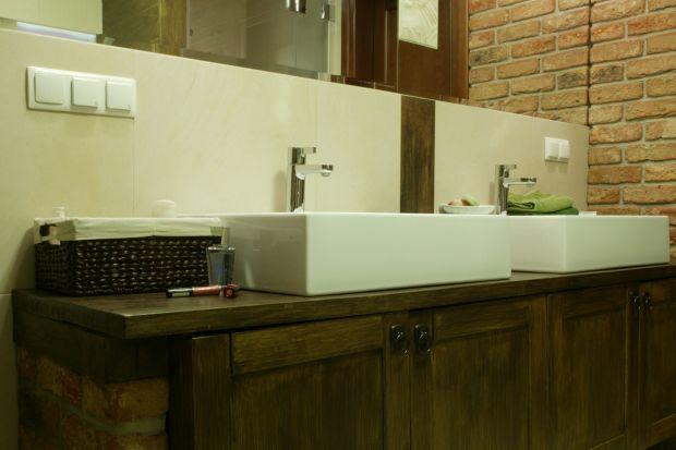 Drewniana komoda, framugi okna oraz wykończenie wnęki nad sedesem czynią wnętrze niezwykle klimatycznym i ciepłym zarazem. Także rustykalna cegła dodaje łazience charakteru.