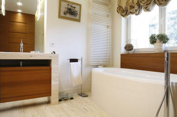 Elegancka aranżacja salonu kąpielowego pani i pana domu zachwyca harmonią i lekkością. Egzotyczne drewno oraz naturalny trawertyn czynią ją bardzo ciepłą i przytulną.