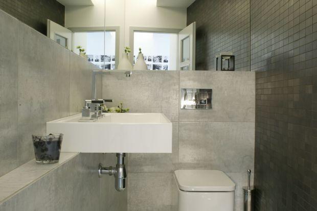 Aranżacja tej niewielkiej toalety nawiązuje do minimalistycznego stylu oraz nowoczesnego designu. Szarość ścian to nawiązanie do stylu ubierania się właścicieli – zwolenników ciemnych barw.