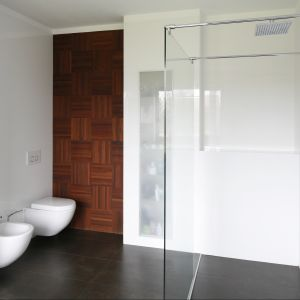 Zastosowanie drewna ociepla wizerunek wnętrza. Na ścianie: mozaika przemysłowa merbau olejowana, w układzie mozaikowym. Fot. Bartosz Jarosz