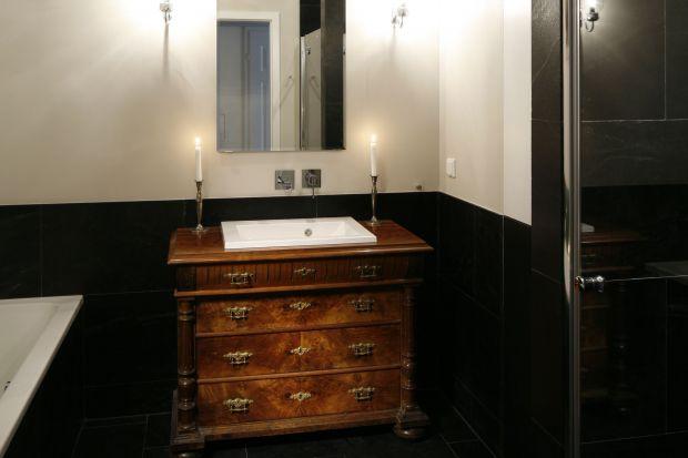 Piękny, kryształowy żyrandol, stylowa komoda z XIX wieku i klimatyczny obraz dodają łazience przy sypialni szlachetnego, pałacowego uroku.