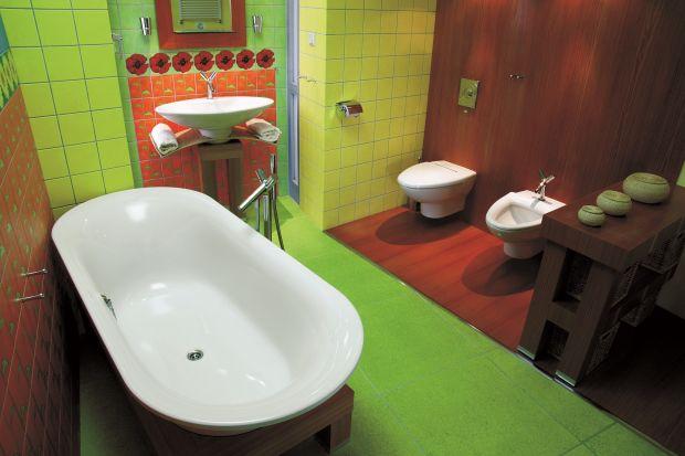 Szlachetny odcień modrzewiowego drewna oraz kolorowe płytki ceramiczne z kwiatami maków i słoneczników tworzą tutaj niezwykłe tło dla eleganckich urządzeń sanitarnych.