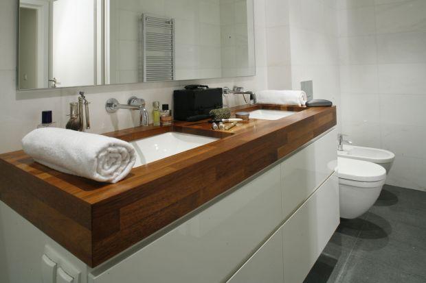 W łazience, o niełatwym do zagospodarowania kształcie, najważniejsze było zapewnienie podstawowych funkcji pomieszczenia. Zadbano także o efekt wizualny: uwagę skupia masywny blat w drewna merbu.