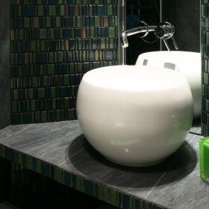 Okrągła biała umywalka (Marmorin Perła) pięknie prezentuje się w otoczeniu zielonej mozaiki i szarych płytek. Dobrana do niej prosta w formie bateria (Kludi  Bozz) wypada równie ciekawie. Fot. Bartosz Jarosz