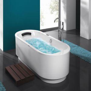 Obok owalnej wanny marki Sanplast z serii WOW/FREE znajdują się puszyste, niebieskie dywaniki. Fot. Sanplast