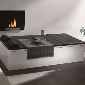 W cieple kominka można wypoczywać nie tylko w kąpieli. Specjalne poduszki tworzą tutaj szezlong z wanny firmy Kaldewei. Fot. Kaldewei