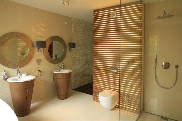 Nowoczesny i przestronny salon kąpielowy, za sprawą kolorów oraz materiałów, jak też światła słonecznego docierającego przez duże okno, jest jasny i pogodny, a o poranku wręcz spowity słońcem.