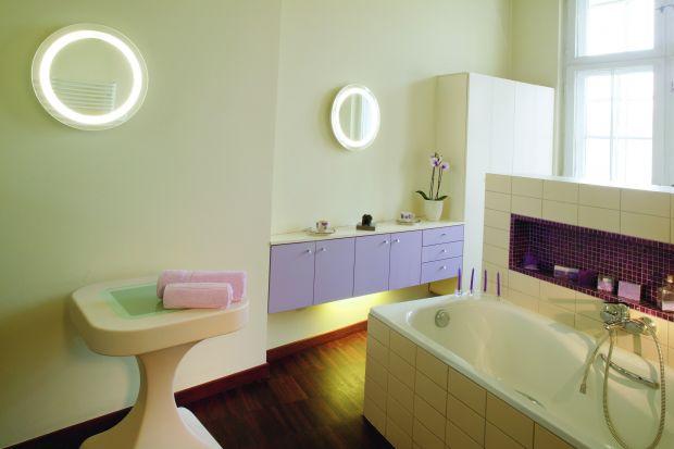Przez każdą kostkę fioletowej mozaiki ze szkła przewija się złota nić. Uwodzicielsko mieni się w świetle lamp-luster, zapraszając do spędzenia czasu w łazience –ot, choćby przy kawie.